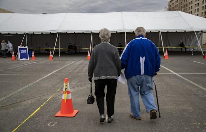RIVERSIDE, CA - FEBRUARY 1, 2021: Robert Nelson,81, of Riverside holds his wife Norma's hand as they walk to the observation lounge area after he received the Moderna vaccination in the parking lot of the Riverside Convention Center on February 1, 2021 in Riverside, California. Norma,83, received her vaccination a couple days earlier. Currently, this site is capable of giving 500 vaccinations a day in one of the regions hardest hit by the pandemic. Only residents 65 and older and educators are eligible for the vaccination here.(Gina Ferazzi / Los Angeles Times)