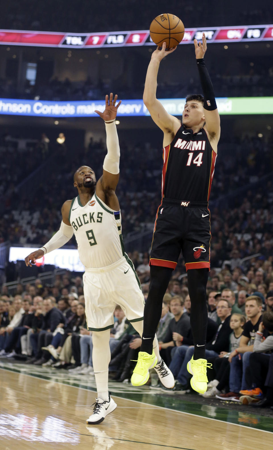 Miami Heat's Tyler Herro (14) puts up a shot against the Milwaukee Bucks' Wesley Matthews (9) during the first half of an NBA basketball game Saturday, Oct. 26, 2019, in Milwaukee. (AP Photo/Jeffrey Phelps)