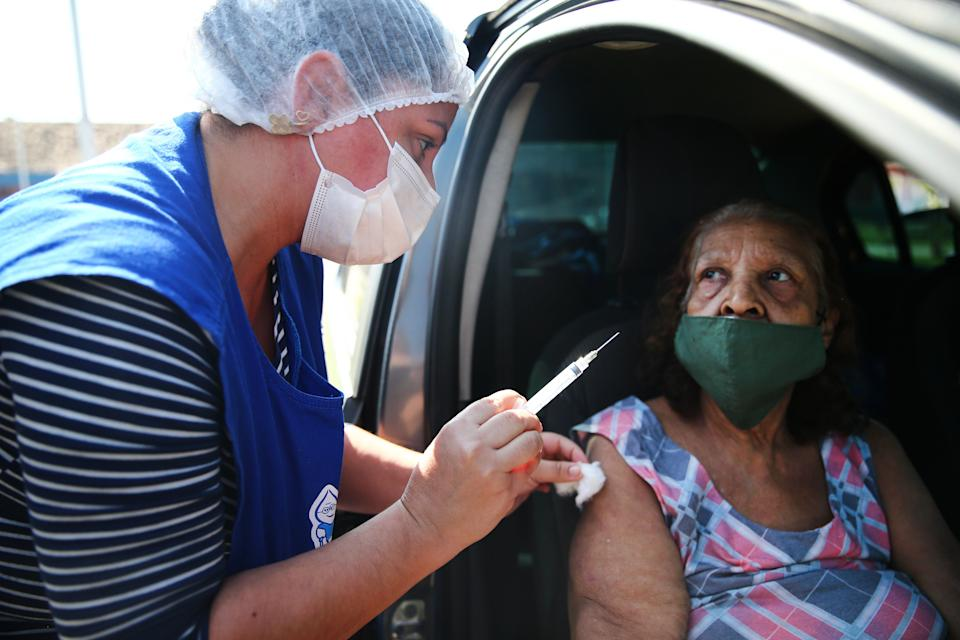 RIO DE JANEIRO, BRAZIL - MAY 26: Public health nurse Ana Maria Basilio holds the empty syringe after administering a COVID-19 vaccination dose to Neide Ferreira de Lima, 79, in the Manguinhos favela community on May 26, 2021 in Rio de Janeiro, Brazil. COVID-19 has now killed more than 1 million people in Latin America and the Caribbean, with nearly half of those killed in Brazil. Only three percent of the population of Latin America have been fully vaccinated against COVID-19. Health experts are warning that Brazil should brace for a new surge of COVID-19 amid a slow vaccine rollout and relaxed restrictions. 450,000 people have been killed in Brazil by COVID-19, second only to the U.S.  (Photo by Mario Tama/Getty Images)