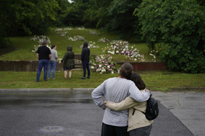 Ana Nunez, right, and Connor Coney embrace as they visit a makeshift memorial beside stairs leading to a now empty lot near the historic Greenwood district during centennial commemorations of the Tulsa Race Massacre, Monday, May 31, 2021, in Tulsa, Okla. (AP Photo/John Locher)