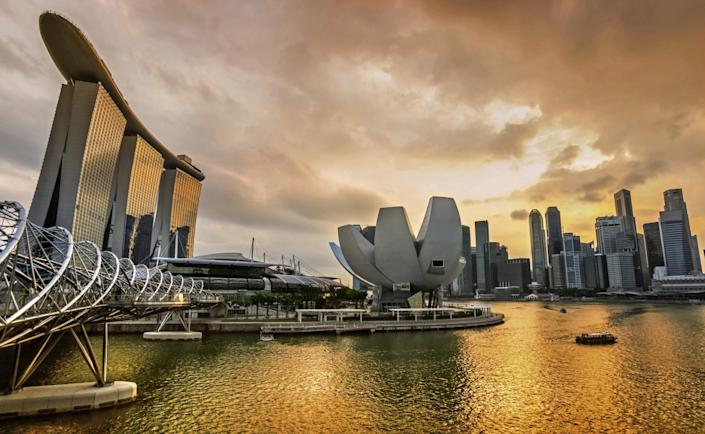 """The dramatic Singapore city skyline at sunset, with the striking Marina Bay Sands Hotel to the left, three towers with a Skypark atop them. <span class=""""copyright"""">(MasterLu / Getty Images)</span>"""