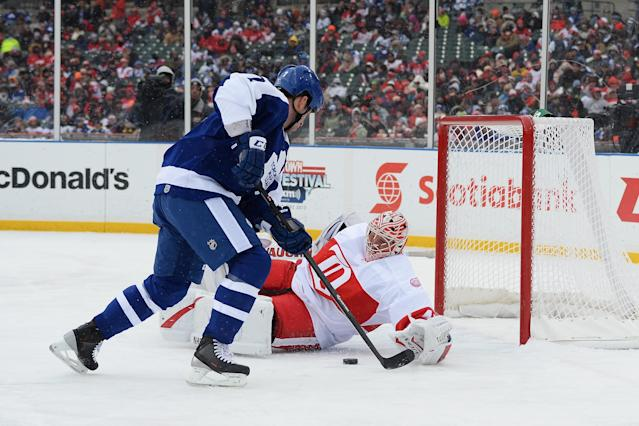 DETROIT, MI - DECEMBER 31: Goaltender Eddie Mio #41 of the Detroit Red Wings stops a shot from Dave McLlwain #7 of the Toronto Maple Leafs in the first period during the 2013 Hockeytown Winter Festival Alumni Showdown on December 31, 2013 at Comerica Park in Detroit, Michigan. (Photo by Jamie Sabau/Getty Images)