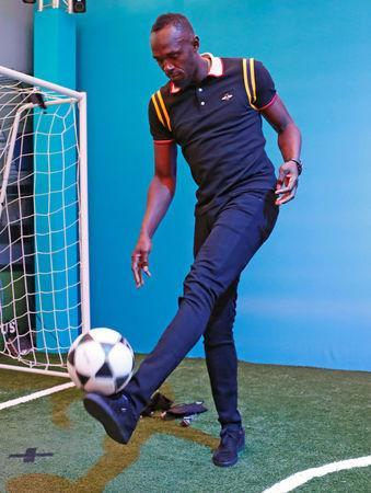 FILE PHOTO: Gold Coast 2018 Commonwealth Games - Gold Coast, Australia - April 12, 2018. Former Jamaican sprinter Usain Bolt kicks a soccer ball during a press conference. REUTERS/David Gray/File Photo