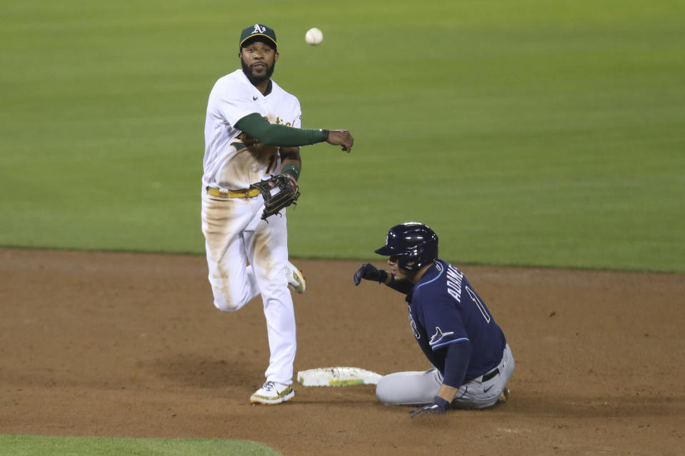 Oakland Athletics' Elvis Andrus throws to first as Tampa Bay Rays' Randy Arozarena slides into second on a ball hit by Yandy Diaz, who was safe during the seventh inning of a baseball game in Oakland, Calif., Friday, May 7, 2021. (AP Photo/Jed Jacobsohn)