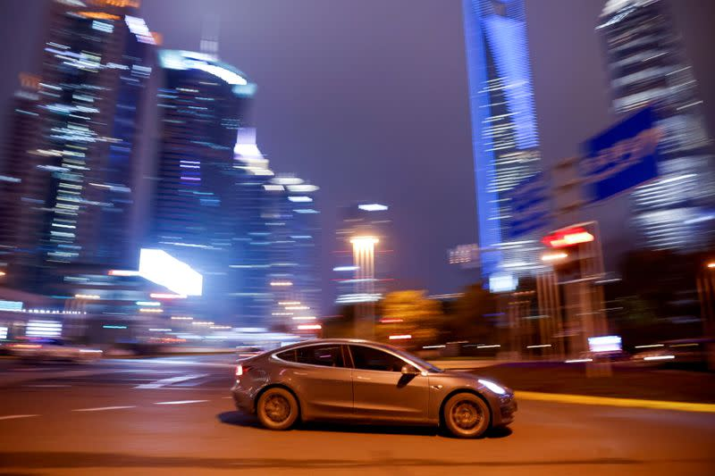 FILE PHOTO: A Tesla electric car drives past a crossing in Shanghai