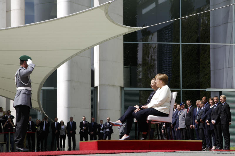 German Chancellor Angela Merkel, center right, and Danish Prime Minister Mette Frederiksen, center left, sit on chairs as they listen to the national anthems during a welcome ceremony for a meeting at the chancellery in Berlin, Thursday, July 11, 2019. German Chancellor and the visiting Danish prime minister sit through their countries' national anthems at a ceremony in Berlin, a day after the latest of three incidents in which Merkel's body shook as she stood during the ceremony. (AP Photo/Markus Schreiber)