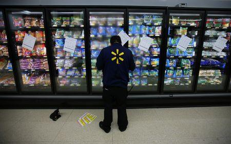 A worker prepares the frozen food section at a newly built Walmart Super Center prior to its opening in Compton, California