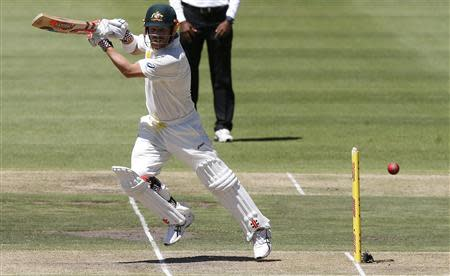 Australia's David Warner plays a shot on the first day of their third test cricket match against South Africa in Cape Town, March 1, 2014. REUTERS/Mike Hutchings