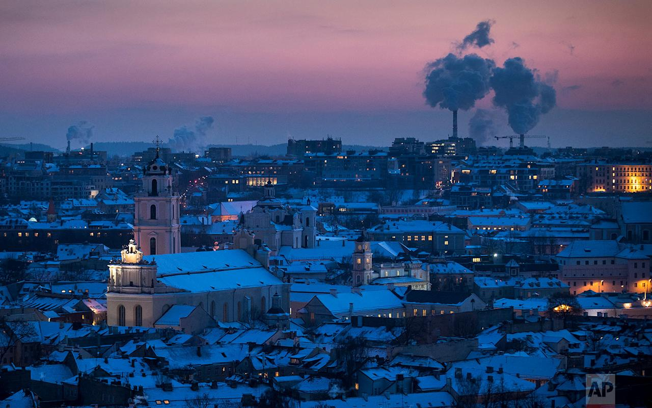 <p>Smoke rises from chimneys during a freezing winter evening over snow covered Vilnius, Lithuania. The air temperature was -15 degrees Celsius (5 degrees Fahrenheit). (AP Photo/Mindaugas Kulbis) </p>