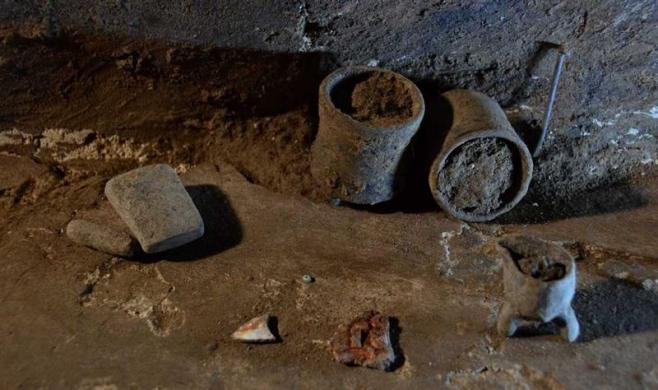 Glasses, a metate (mealing stone) and a sea shell fragment are seen at a burial chamber at the archeological site of Atzompa, in the Mexican state of Oaxaca in this undated handout photo released by the National Institute of Anthropology and History (INAH) on July 18, 2012. A funerary complex, consisting of three burial chambers, was discovered at the pre-Hispanic site of Atzompa in Oaxaca. The discovery of the complex, which is more than 1,100 years old, is important because it was located inside a building designed exclusively to house a series of tombs, which are placed vertically, one above another, and unlike the ones found so far, they are not underground, according to INAH.