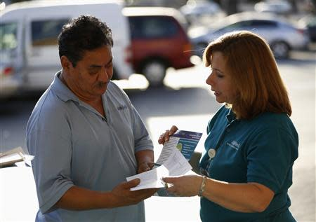 Engrith Acosta, patient care coordinator at AltaMed, speaks to a man during a community outreach on Obamacare in Los Angeles, California November 6, 2013. REUTERS/Mario Anzuoni