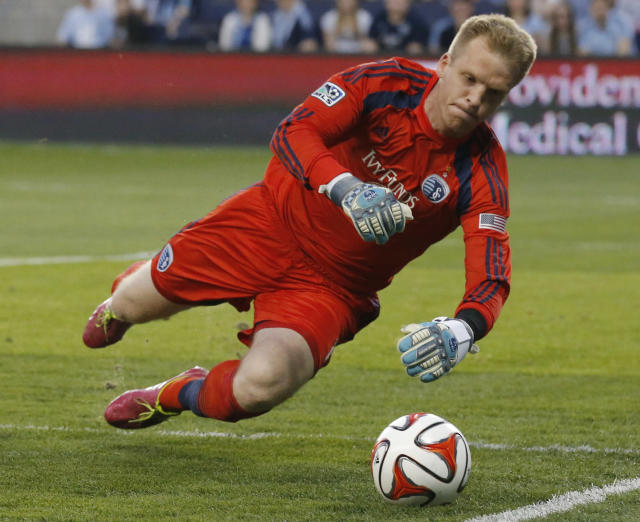 Sporting Kansas City goalkeeper Eric Kronberg dives for the ball during the first half of an MLS soccer match against the Montreal Impact in Kansas City, Kan., Saturday, April 19, 2014. Impact was awarded a corner-kick on the play. (AP Photo/Orlin Wagner)