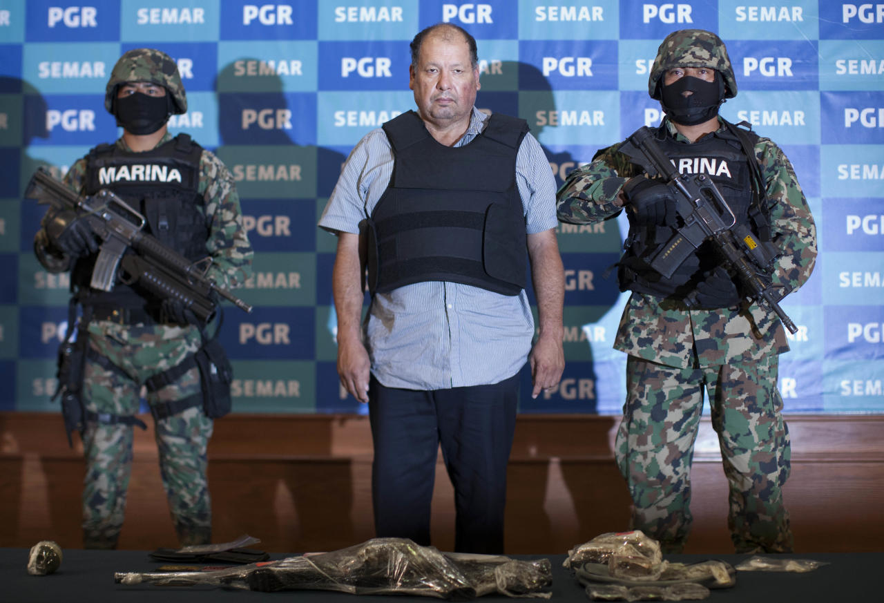 """Mexican Navy officers flank Mario Cardenas Guillen, also known as """"El Gordo"""" and """"M-1,"""" during his presentation to the media in Mexico City, Tuesday, Sept. 4, 2012. Authorities says Cardenas Guillen, a top leader of the Gulf drug cartel, is the brother of Osiel Cardenas Guillen, who led the cartel until he was detained in 2003. Osiel Cardenas was extradited in 2007 to the United States and sentenced to 25 years in prison. (AP Photo/Alexandre Meneghini)"""