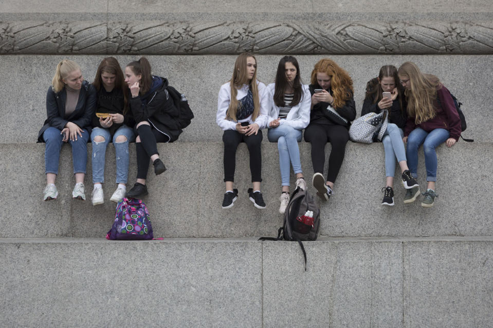 Young women visitors to the capital sit beneath Nelson's Column with a view across Trafalgar Square and look at their mobile phones, on 20th May 2019, in London, England.