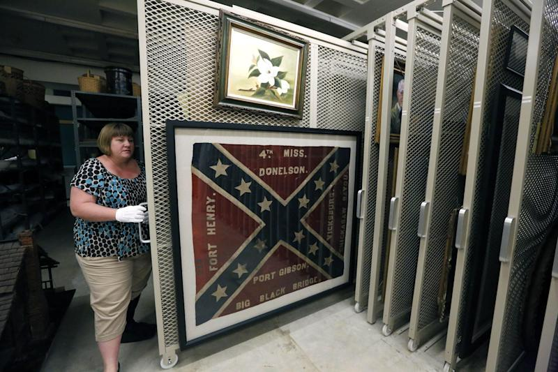 In this Oct. 11, 2013 photograph, Cindy Gardner, Director of Collections and Museum Division Project Manager, for the Museum of Mississippi History at the Mississippi Department of Archives and History shows off a Confederate battle flag and era painting that will be among the items that will eventually be displayed in the state history museum that will be built along side a museum documenting civil rights in the state, in Jackson, Miss. The two museums will have more than 200,000 square feet combined and are to be built not far from the Capitol in Jackson. The state has committed $40 million to the museums, and Hank Holmes said officials are trying to raise $14 million in private donations. (AP Photo/Rogelio V. Solis)