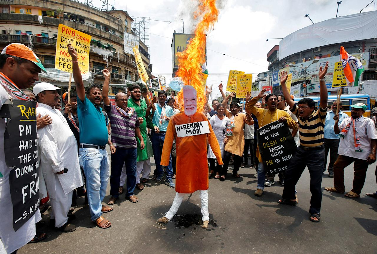 Supporters of India's main opposition Congress party shout slogans as they burn an effigy depicting India's Prime Minister Narendra Modi during a protest against the rise in fuel prices, in Kolkata, India, May 26, 2018. REUTERS/Rupak De Chowdhuri     TPX IMAGES OF THE DAY
