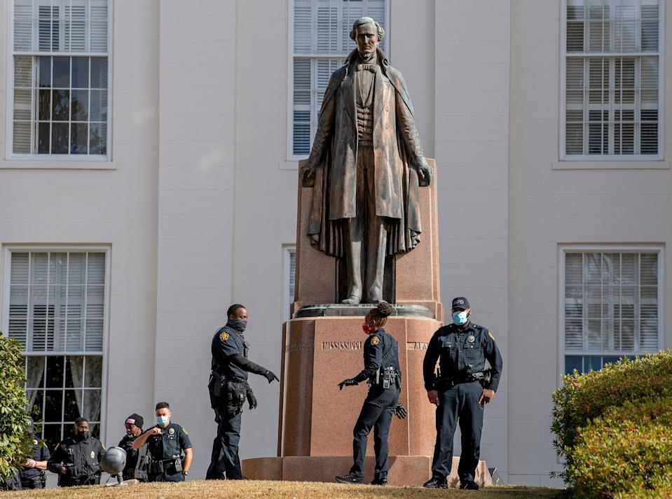 Montgomery Police officers patrol the Alabama state capitol building in downtown Montgomery, Ala., on Jan. 17, 2021. Protestors have threatened to march on all state capitols in the country. The statue is of Confederate President Jefferson Davis.
