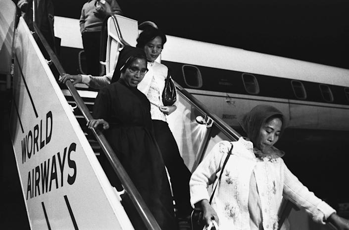 Refugees from Vietnam descend a flight of stairs from an airplane in Oakland, California, April 1975 | Ted Streshinsky—Corbis/Getty Images