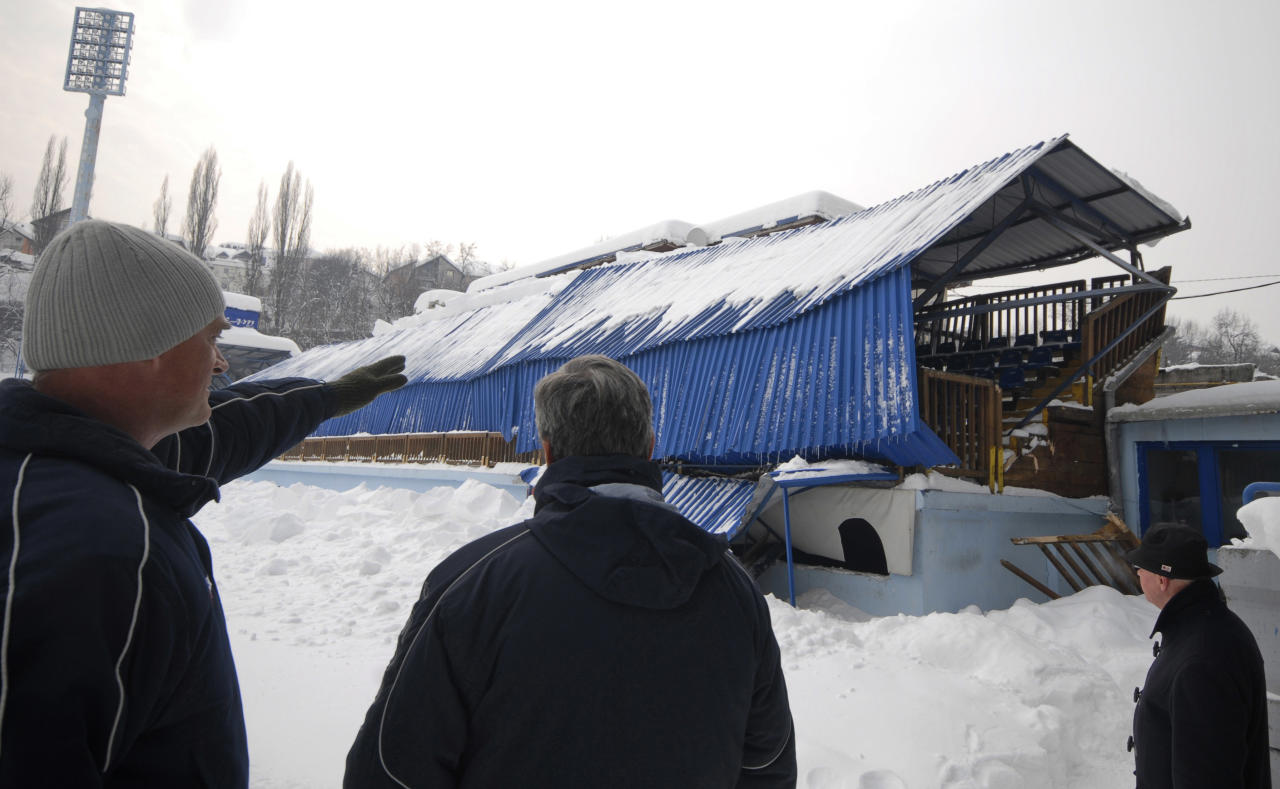 Bosnian workers inspect the collapsed roof of the Grbavica stadium, in Sarajevo, Bosnia, on Monday, Feb. 13, 2012. The roof of a stand of a Sarajevo stadium collapsed under the weight of heavy snow but nobody was injured. The incident occurred a day after the roof of the sports center Skenderija _ used for ice skating events at the 1984 Winter Olympics in Bosnia _ collapsed, also causing no injuries as the complex was closed on Sunday. (AP Photo/Sulejman Omerbasic)