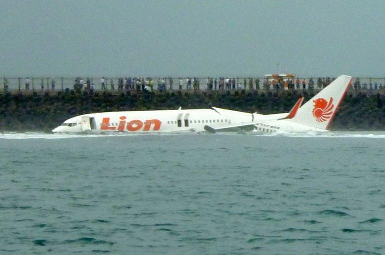 A Lion Air Boeing 737 lies submerged in the water after skidding off the runaway during landing at Bali's international airport near Denpasar on April 13, 2013. An Indonesian plane carrying 101 passengers broke in two after missing the runway at Bali airport Saturday and landing in the sea, leaving dozens injured but no fatalities