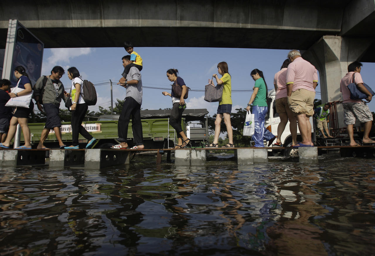 FILE - In this Thursday, Nov. 10, 2011 file photo, pedestrians use an elevated makeshift walkway to avoid the floodwaters in Bangkok, Thailand. The year 2011 brought a record heat wave to Texas, massive floods in Bangkok and an unusually warm November in England. How much has global warming boosted the chances of events like that? Quite a lot in Texas and England, but apparently not at all in Bangkok, according to new analyses released Tuesday, July 10, 2012. It found no sign that climate change played a role in that event, noting that the amount of rainfall was not very unusual. The scale of the flooding was influenced more by factors like reservoir operation policies, researchers wrote. (AP Photo/Aaron Favila)
