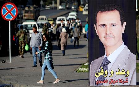 FILE PHOTO: A woman walks near a picture of Syrian President Bashar al Assad in Damascus.