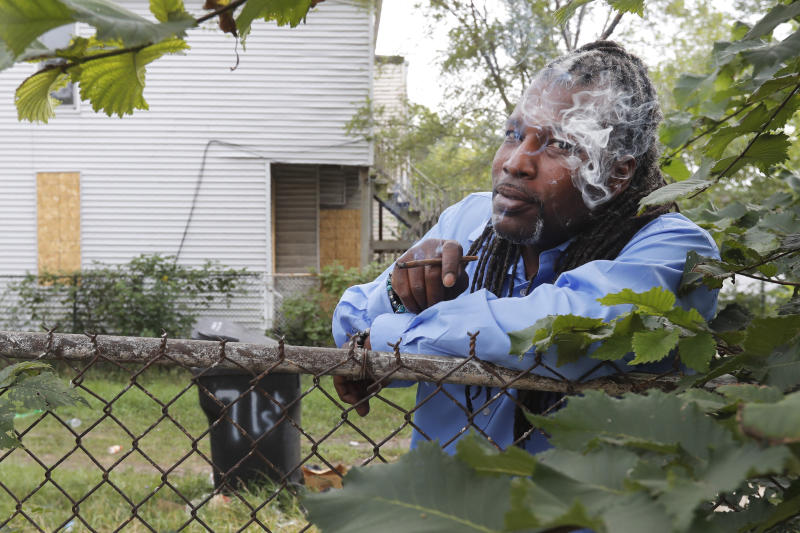 """Willie """"J.R."""" Fleming, director of the Chicago Anti-Eviction Campaign and who helped organize a nonprofit called Hemp in the Hood smokes his medicinal marijuana cigarette in a vacant lot next to a boarded up home on the Southside of Chicago, Thursday, Sept. 19, 2019. A hopeful social-equity applicant, Fleming has already begun asking established marijuana companies, among them the early licensees in Illinois, """"to share their wealth."""" """"Not always in cash, but in resources,"""" said Fleming. (AP Photo/Charles Rex Arbogast)"""