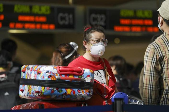 "An LAX passenger, mask in place, lines up on May 22. <span class=""copyright"">(Irfan Khan / Los Angeles Times)</span>"