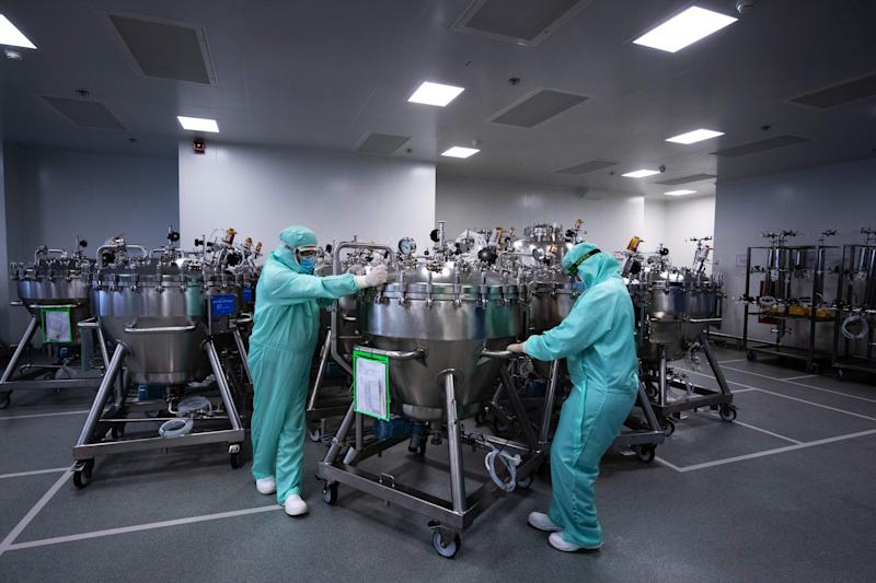 Lab technicians dedicated to the vaccines formulation, wearing Personal Protective Equipment (PPE), move stainless steel tanks for manufacturing vaccines preparations before the syringe filling phase, at a French pharmaceutical company Sanofi's world distribution centre in Val-de-Reuil on July 10, 2020. (Photo by JOEL SAGET / AFP) (Photo by JOEL SAGET/AFP via Getty Images)