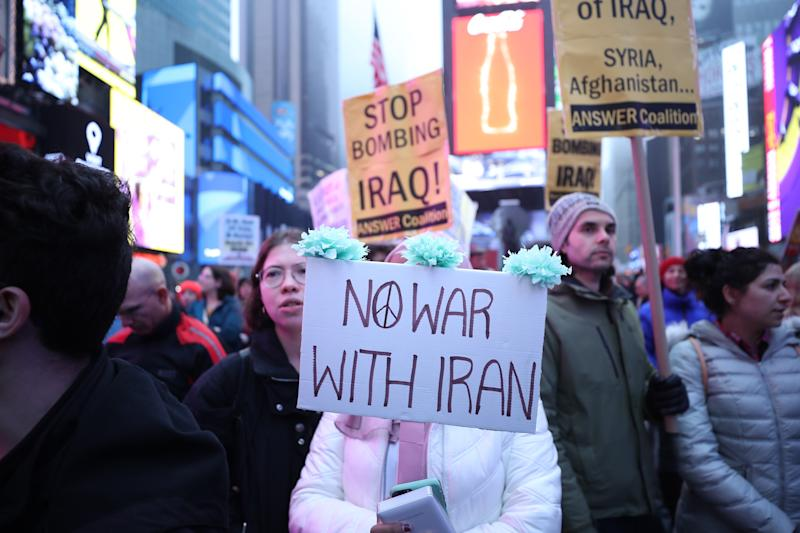 NEW YORK, USA - JANUARY 04 : Anti-war activists hold banners during a protest organised by 'Answer Coalition' at Times Square following the killing of Iranian Revolutionary Guards' Quds Force commander Qasem Soleimani by a US airstrike in the Iraqi capital Baghdad, on January 4, 2020 in New York, United States. (Photo by Tayfun Coskun/Anadolu Agency via Getty Images)