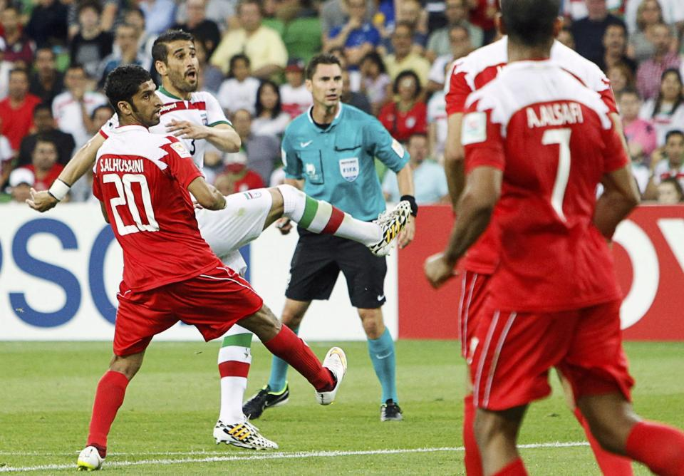 Iran's Ehsan Hajisafi (2nd L) shoots to score a goal next to Bahrain's Sami Al-Husaini during their Asian Cup Group C soccer match at the Rectangular stadium in Melbourne January 11, 2015. REUTERS/Brandon Malone (AUSTRALIA - Tags: SOCCER SPORT)
