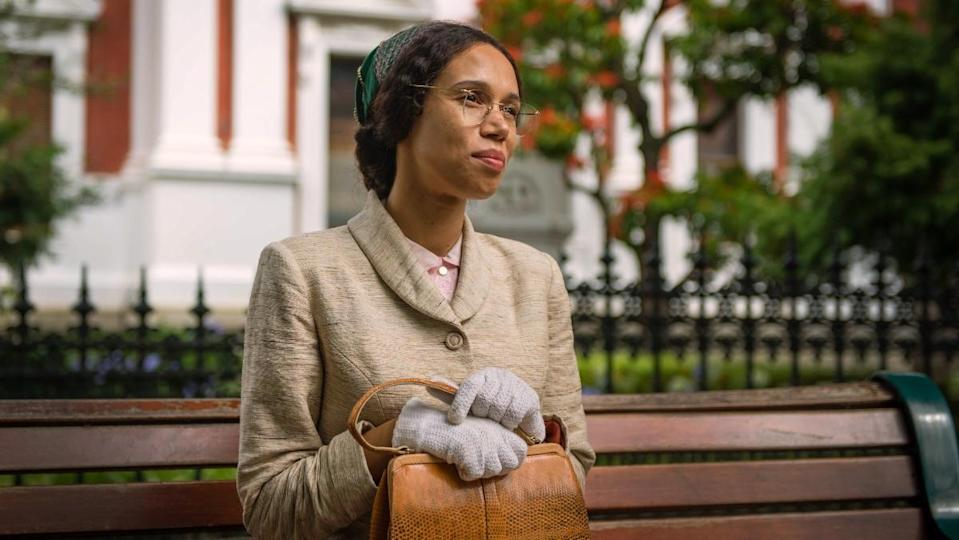 a photo of an actress portraying Rosa Parks sitting on a bench wearing glasses, a small dark hat, and a beige suit with a brown purse