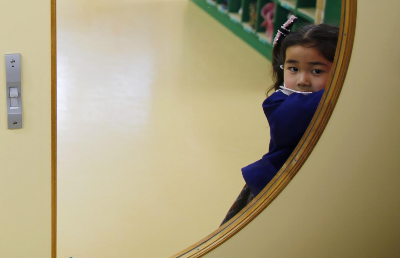A girl opens the door of a teacher's staff room at the Emporium kindergarten in Koriyama, west of the tsunami-crippled Fukushima Daiichi nuclear power plant, Fukushima prefecture February 28, 2014. March 11 marks the third anniversary of the earthquake and tsunami that devastated Japan�s Fukushima Daiichi nuclear power plant. In Koriyama, a short drive from the crippled Fukushima nuclear plant, the city recommended shortly after the disaster that children up to two years old not spend more than 15 minutes outside each day. Those aged 3 to 5 should limit their outdoor time to 30 minutes or less. The limits were lifted last year, but many kindergartens and nursery schools continue to obey them even now in line with the wishes of worried parents. An annual survey by the Fukushima prefecture Board of Education found that children in Fukushima weighed more than the national average in virtually every age group. The cause seems to be a lack of exercise and outdoor activity. Picture taken February 28, 2014. REUTERS/Toru Hanai (JAPAN - Tags: DISASTER EDUCATION ENVIRONMENT HEALTH)