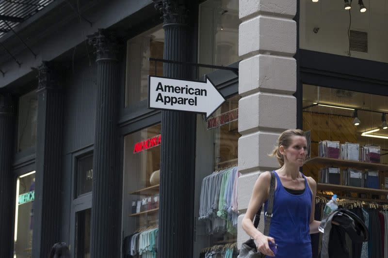 A woman walks past an American Apparel store in New York