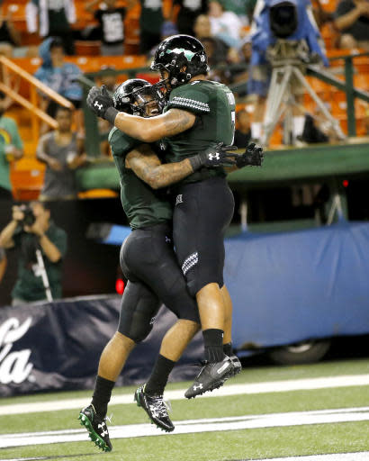 Hawaii running back Fred Holly III (21) and running back Dayton Furuta (7) celebrate in the end zone after Holly III made a touchdown over Duquesne during the third quarter of an NCAA college football game Saturday, Sept. 22, 2018, in Honolulu. (AP Photo/Marco Garcia)