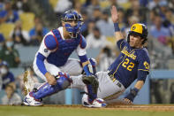 Milwaukee Brewers' Christian Yelich slides in to home to score off of a double hit by Eduardo Escobar during the third inning of a baseball game against the Los Angeles Dodgers Friday, Sept. 1, 2021, in Los Angeles. Los Angeles Dodgers catcher Austin Barnes is at left. (AP Photo/Ashley Landis)