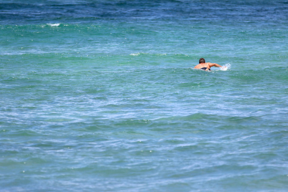 Isaiah Helekunihi Walker, a Native Hawaiian historian and professor, paddles out to surf in Laie, Hawaii, Thursday, July 8, 2021. For some Native Hawaiians, surfing's Olympic debut is both a celebration of a cultural touchstone invented by their ancestors, and an extension of the racial indignities seared into the history of the game and their homeland. (AP Photo/Caleb Jones)