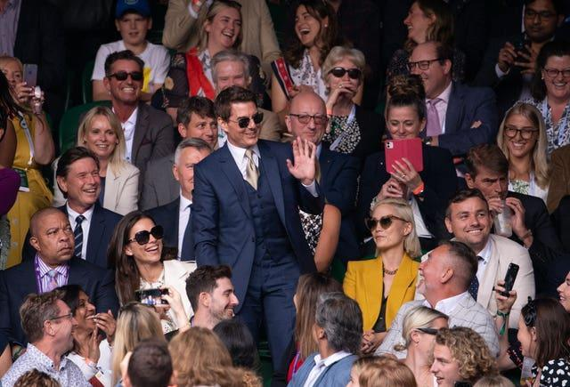 Tom Cruise (centre) waves to the fans at Wimbledon