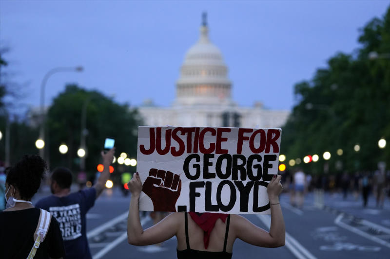 Demonstrators walk along Pennsylvania Avenue as they protest the death of George Floyd, a black man who died in police custody in Minneapolis, Friday, May 29, 2020, in Washington. (AP Photo/Evan Vucci)