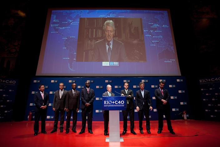 A live image of former President Bill Clinton is projected as he speaks with mayors, from left to right, Won Soon Park of Seoul, Ecktar Wuerzner of Heidelberg, Babatunde Fashola of Lagos, Franklyn Tau of Johannesburg, Michael Bloomberg of New York, Eduardo Paes of Rio de Janeiro, Eduardo Macri of Buenos Aires and Eduardo Kassab of Sao Paulo, during the Rio+C40 meeting, a parallel event during the UN Conference on Sustainable Development, or Rio+20, in Rio de Janeiro, Brazil, Tuesday, June 19, 2012. While squabbling between rich and poor countries threatens to derail the Earth summit, the world's mayors say they can't afford the luxury of endless, fruitless negotiations and are already taking real action to stave off environmental disaster and preserve natural resources for future generations. (AP Photo/Felipe Dana)