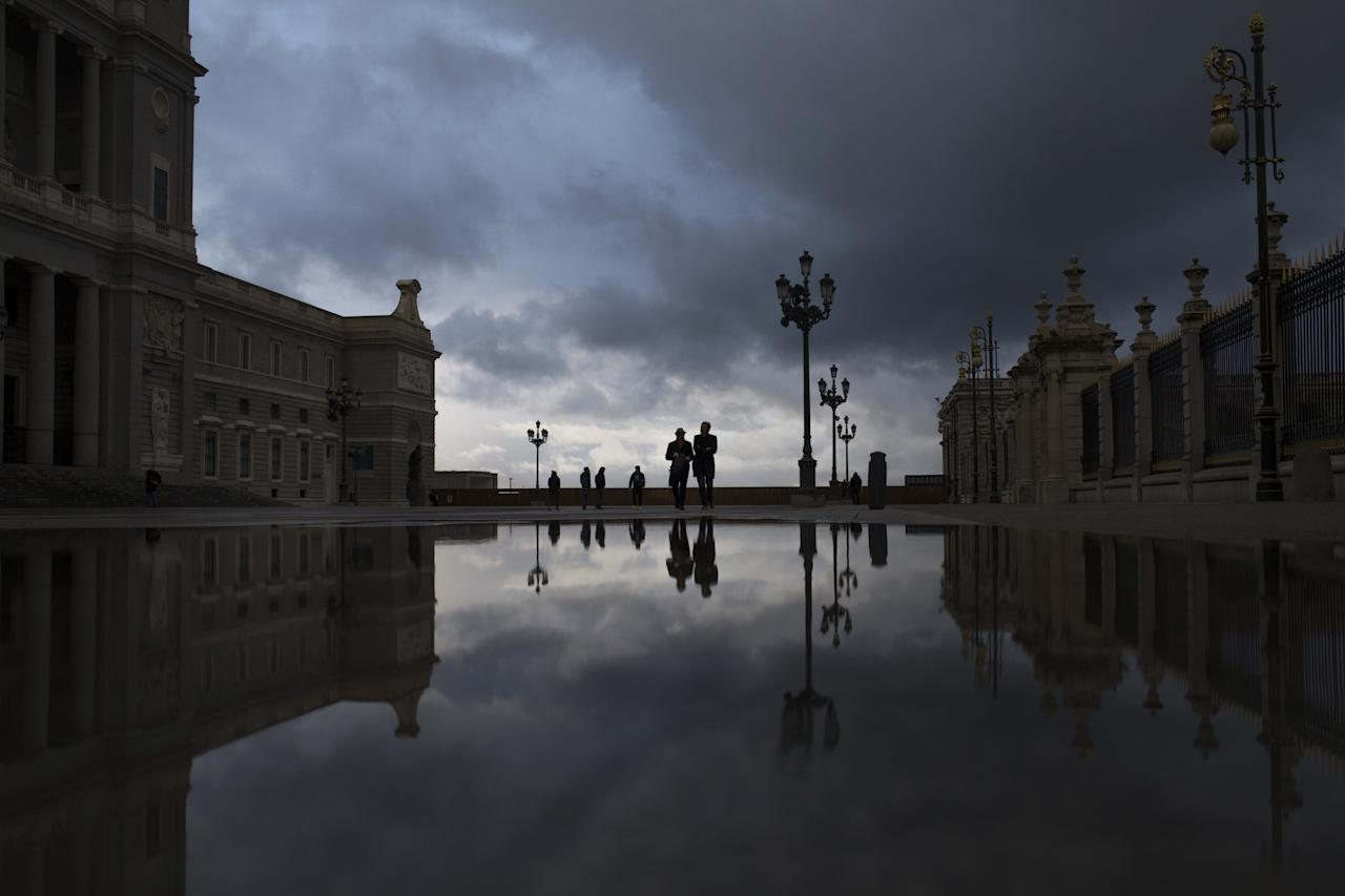 <p>People stroll along the square located between La Almudena cathedral, left, and the Royal Palace, right, during a raining evening in Madrid, Wednesday, March 22, 2017. The place, mostly visited by tourists, is a novel area of the Spanish capital located nearby to the Opera house.(AP Photo/Francisco Seco) </p>