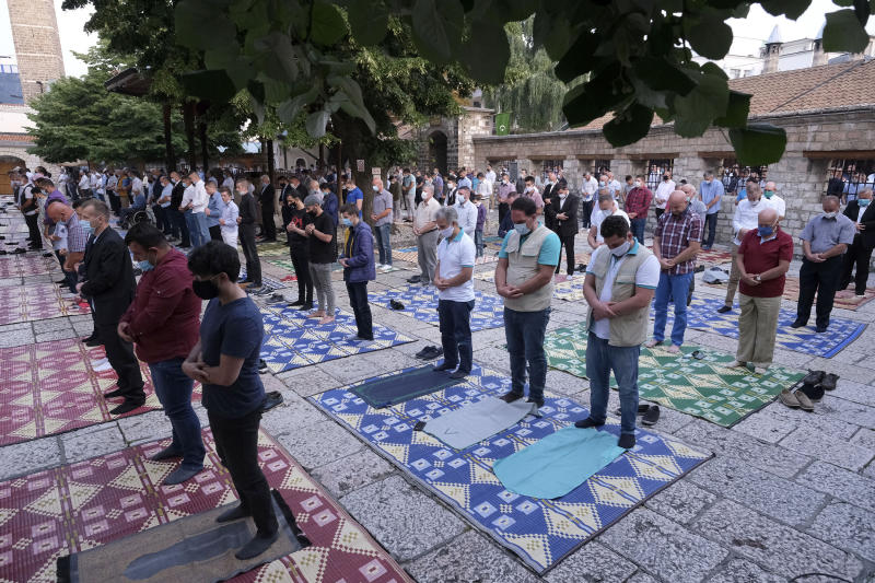Worshippers wearing masks to help stop the spread of the coronavirus, offer Eid al-Adha prayer while maintaining a social distance in front of the Gazi Husrev-beg mosque in Sarajevo, Bosnia, Friday, July 31, 2020. Eid al-Adha, or Feast of Sacrifice, Islam's most important holiday, marks the willingness of the Prophet Ibrahim to sacrifice his son. (AP Photo/Kemal Softic)