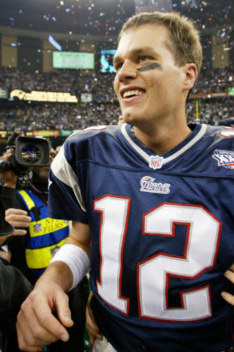 """FILE - In this Feb. 3, 2002, file photo, New England Patriots quarterback Tom Brady smiles after the Patriots defeated the St. Louis Rams 20-17 in NFL football's Super Bowl XXXVI in New Orleans. A pair of Super Bowl winning teams that launched dynasties in San Francisco and New England highlighted the list of the NFL's greatest teams, numbers 31-100. The Patriots won a surprise title in 2001 after the untested Brady took over from the injured Drew Bledsoe early in the season. New England needed a favorable ruling and dramatic kick by Adam Vinatieri to win the """"Tuck Rule"""" game against Oakland, won at Pittsburgh in the AFC championship game and slowed down the dynamic Rams offense for the franchise's first title. That team ranked 51st. (AP Photo/Doug Mills, File)"""