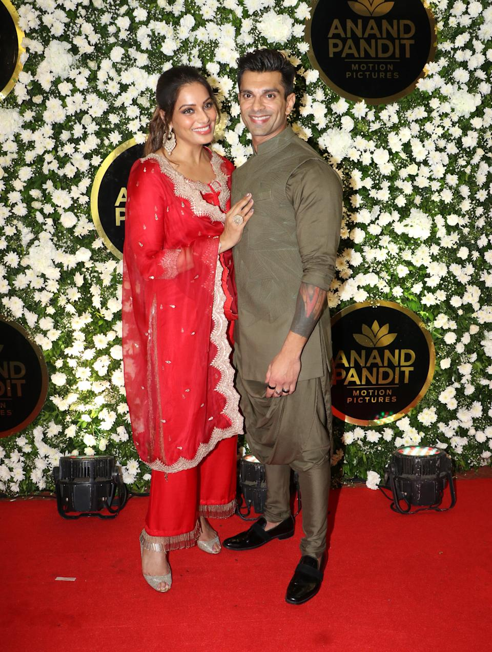 Bipasha Basu looks stunning in red, while Karan Singh Grover is at his ethnic best.