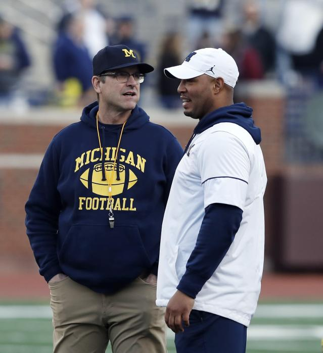 Michigan head coach Jim Harbaugh, left, and offensive coordinator Josh Gattis talk during the team's annual spring NCAA college football game, Saturday, April 13, 2019, in Ann Arbor, Mich. (AP Photo/Carlos Osorio)