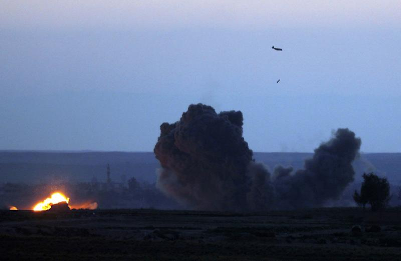 A military plane with the US-backed coalition against IS releases a bomb over the embattled village of Baghouz (AFP Photo/Delil souleiman)