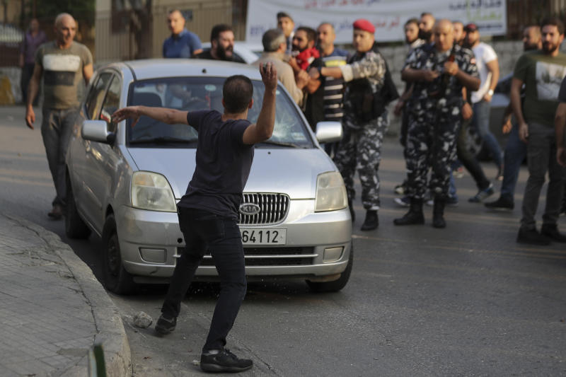Anti-Government protesters throw stones at the car belonging to a supporter of President Michel Aoun, with whom they found an automatic rifle used in a shooting in the town of Jal el-Dib, north of Beirut, Lebanon, Wednesday, Nov. 13, 2019. A man opened fire over the heads of protesters in a town north of Beirut Wednesday, the second shooting incident in as many days as tensions rise in Lebanon between supporters and opponents of President Michel Aoun amid nationwide protests. (AP Photo/Hassan Ammar)