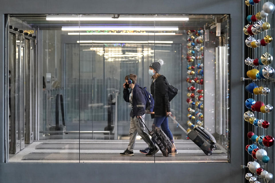 FILE - In this Sunday, Nov. 29, 2020 file photo, travelers walk through Terminal 3 at O'Hare International Airport in Chicago. The Transportation Security Administration said nearly 1.2 million people went through U.S. airports on Sunday, the highest number since the coronavirus pandemic gripped the country back in March, despite the pleadings of public health experts for people to stay home over Thanksgiving. (AP Photo/Nam Y. Huh, File)