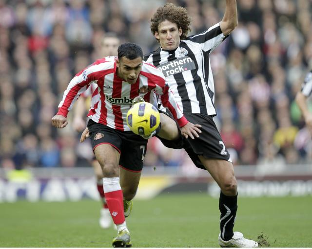 Sunderland's Egyptian midfielder, Ahmed Elmohamady (L) vies with Newcastle United's Argentinean defender, Fabricio Coloccini (R) during an English FA Premier League football match at the Stadium of Light, Sunderland, England, on January 16, 2011. AFP PHOTO/GRAHAM STUART - FOR EDITORIAL USE ONLY Additional licence required for any commercial/promotional use or use on TV or internet (except identical online version of newspaper) of Premier League/Football League photos. Tel DataCo +44 207 2981656. Do not alter/modify photo. (Photo credit should read GRAHAM STUART/AFP/Getty Images)