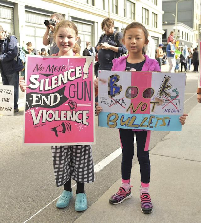 <p>Two girls hold signs in protest at March for Our Lives in Los Angeles. (Photo: Getty Images) </p>